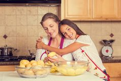 Happy, smiling mother and daughter cooking dinner, preparing food Stock Image
