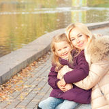 Happy smiling mother and daughter outdoor near lake. Stock Image