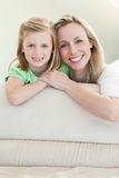 Happy smiling mother and daughter on the sofa Royalty Free Stock Images
