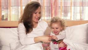 Happy smiling mother with her child girl playing with toy cats on bed. Static shot. 4K UHD stock footage