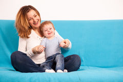 Happy smiling mother and her son on the couch Royalty Free Stock Photography