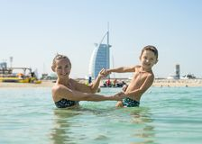 Happy smiling mother and her son playing and running on the beach. Concept of friendly family. Sea Royalty Free Stock Image