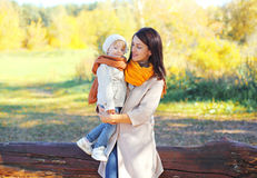 Happy smiling mother holding on hands child in autumn Stock Image