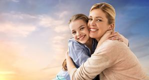 Happy smiling mother hugging daughter over sky Stock Photography