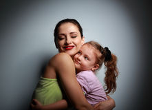 Happy smiling mother hugging her cute girl with love. On dark background with shadows Stock Image