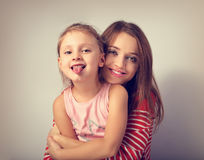 Happy smiling mother hugging with love her frolic grimacing kid Royalty Free Stock Image