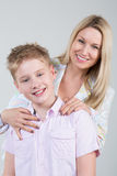 Happy smiling mother hugging young son. With disheveled hair in the studio stock photography