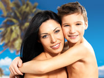 Happy smiling mother hugs son at tropical beach Royalty Free Stock Photos