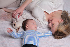 Happy smiling Mother and 3 month old baby boy and dog enjoying at home Stock Image