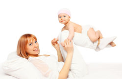 Happy smiling mother playing with baby on the bed Stock Images