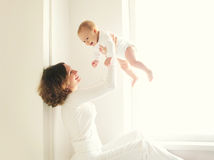 Happy smiling mother playing with baby home in white Stock Photo
