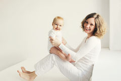 Happy smiling mother playing with baby home in white room Stock Photos