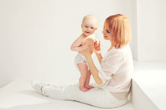 Happy smiling mother playing with baby home in white room Royalty Free Stock Photos