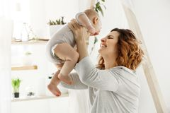 Happy smiling mother playing with newborn child in comfy light bedroom in front of window. Moments of motherhood. Happiness with kids. Family concept stock image