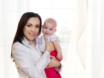 Happy smiling mother with six month old baby girl Royalty Free Stock Photo