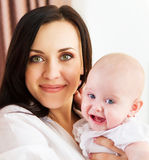 Happy smiling mother with six month old baby girl Stock Photo