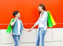 Happy smiling mother and son child with shopping bags having fun in city Royalty Free Stock Image
