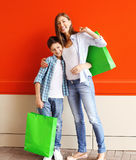Happy smiling mother and son child with shopping bags having fun Stock Photos