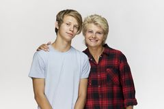 Happy and smiling mother and son. Loving family portrait against white wall royalty free stock photography