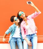 Happy smiling mother with son teenager is taking picture self portrait. On a smartphone on background Royalty Free Stock Photos