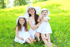 Happy smiling mother and two children wearing white dress and straw hats. On grass summer stock images