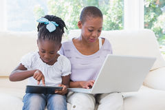 Happy smiling mother using laptop with her daughter using tablet on couch Stock Images