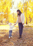 Happy smiling mother walking with child in sunny autumn Stock Photography