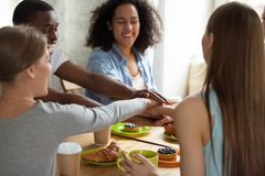 Happy smiling multiracial friends joining hands at meeting in cafe stock image