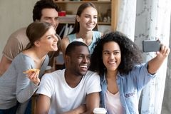 Happy smiling multiracial friends making selfie photo in pizzeria royalty free stock photos