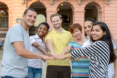 Happy smiling multiracial group of young friends. Touching fingertips in a circle in a gesture of teamwork of friendship Stock Photography