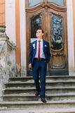 Happy, smiling newlywed groom posing in blue suit on old stairs at vintage building entrance Royalty Free Stock Images