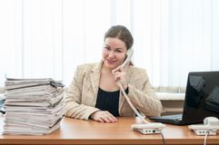 Happy smiling office assistant sitting at desk and calling by telephone Royalty Free Stock Photo