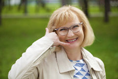 Happy smiling old blonde woman with call me gesture Royalty Free Stock Photos