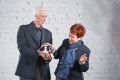 Happy smiling old couple standing together with pet rabbit on white brick background. Royalty Free Stock Photos