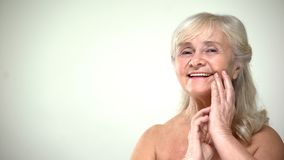 Happy smiling old female touching face, applying anti-aging cream, cosmetology royalty free stock photos