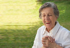 A happy smiling old woman with closed eyes. A happy smiling old woman between 70 and 80 years old is keeping two hands together and is keeping her eyes closed Royalty Free Stock Photos