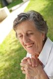 A happy smiling old woman is very surprised to something. A happy smiling old woman between 70 and 80 years old is keeping two hands together sitting in the Royalty Free Stock Image