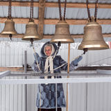 Happy smiling older woman playing the bells in winter day Stock Photos