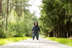 Happy smiling one year baby boy on the walk in the sunny summer park or forest. Concept of first steps stock image