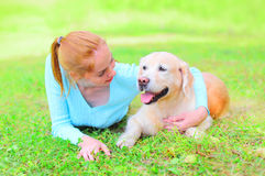 Happy smiling owner woman and Golden Retriever dog is lying Royalty Free Stock Photo