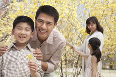 Happy, smiling parents with two children enjoying the park in springtime and looking at flowers Royalty Free Stock Images