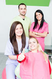 Happy smiling patient with dental team. Showing like royalty free stock photography