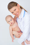 Happy smiling pediatrician/ therapist woman holding lovely child Royalty Free Stock Photo