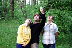 Happy smiling people in forest looking up  Royalty Free Stock Photography