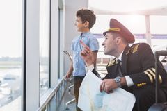 Happy smiling pilot spending time with child. Glad father aviator is squatting near interested son and pointing up. Kid looking through glass wall with smile Stock Image