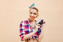 Happy smiling pinup girl in yellow dress using vintage camera Royalty Free Stock Photography