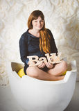 Happy smiling pregnant woman sitting in big egg shell Stock Photo