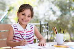 Happy Smiling Preschool Child Girl Drawing Pictures. Outdoors in Garden in Summer Time stock photo