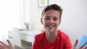 Happy smiling preteen boy talking at home