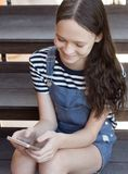 Happy smiling preteen girl sitting on stairs and chatting on the phone. Top view lifestyle shot. Technology generation. Concept Stock Images